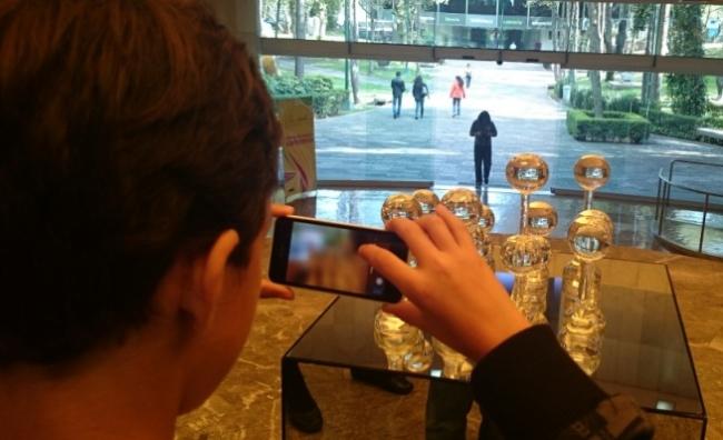 Niño espectador fotografiando una escultura mientras mujer espectador ingresa con cámara fotográfica. Museo de Arte Modeno, Ciudad de México. Foto: Marco A. López Sánchez.